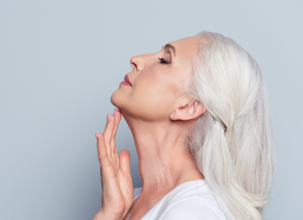 woman raising head by lifting neck with hand