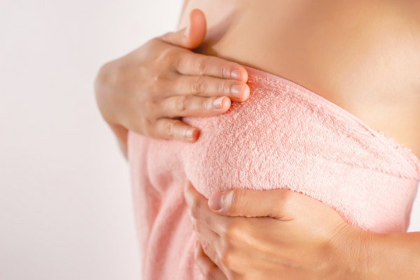 woman covering breasts with towel