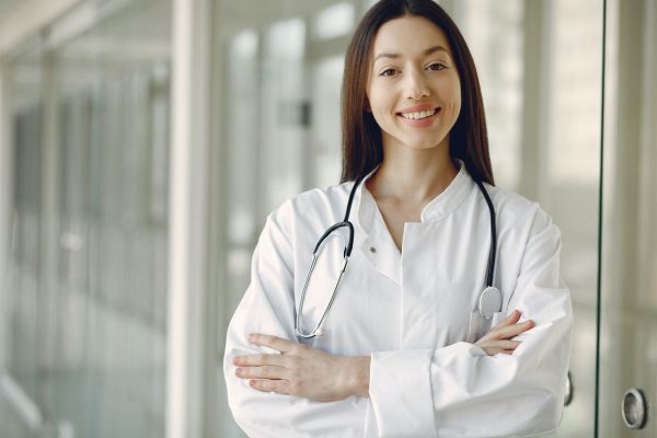surgeon standing with arms folded and smiling at camera